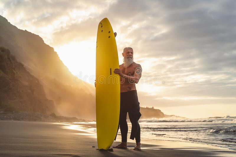 Happy fit senior having fun surfing at sunset time - Sporty bearded man training with surfboard on the beach stock image