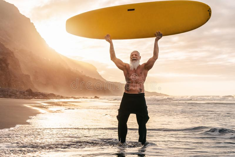 Happy fit senior having fun surfing at sunset time - Sporty bearded man training with surfboard on the beach. Elderly healthy people lifestyle and extreme royalty free stock photos