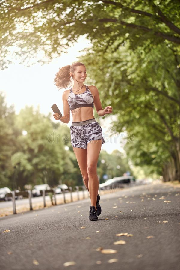 Happy fit slender young woman jogging listening to music stock photos