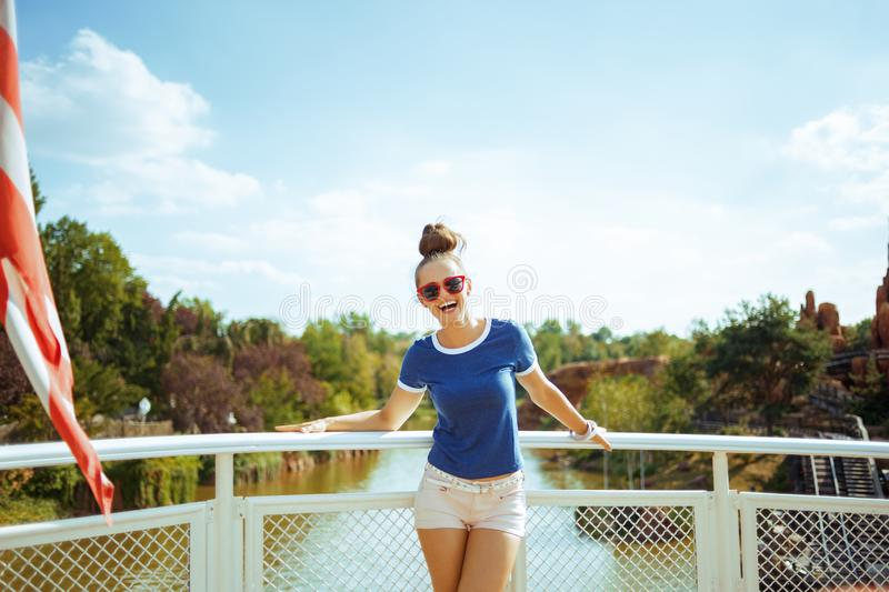 Happy fit solo tourist woman on river boat having river cruise stock photo