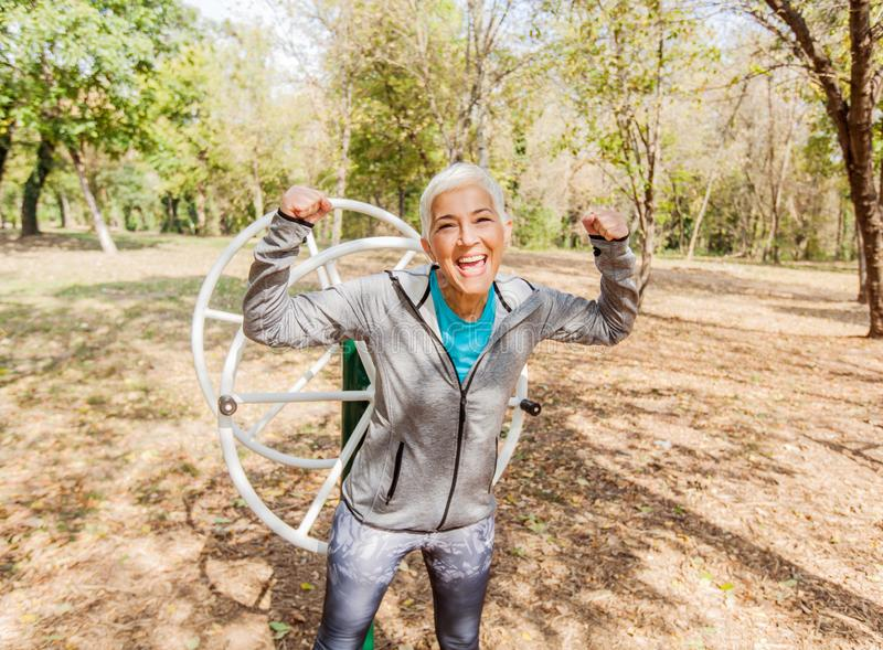 Happy Fit Successful Senior Woman Raised Arms At Outdoor Gym stock photos