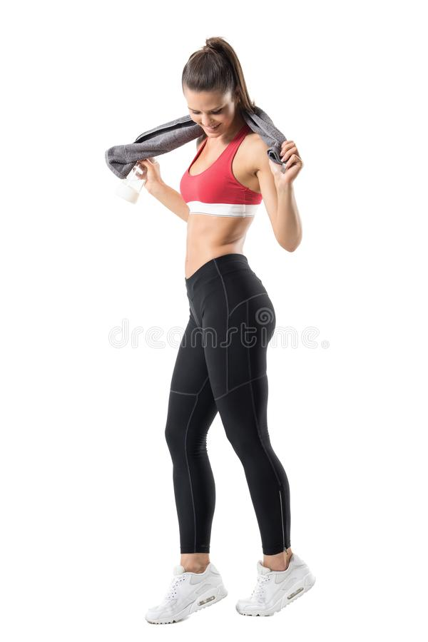 Happy fit woman in top and leggings holding towel around neck smiling and looking down. Full body length portrait isolated on white background royalty free stock image