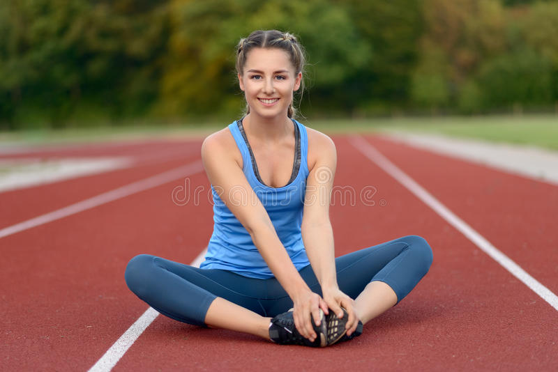 Happy fit young woman doing stretching exercises royalty free stock images