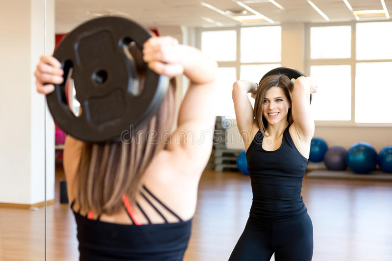 Happy fit young woman in the gym. Lifting plate stock images