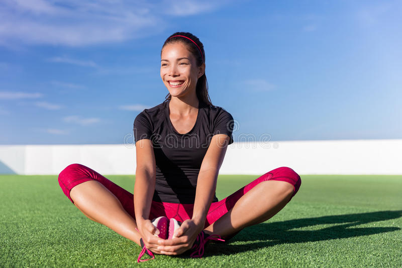 Happy fitness Asian woman stretching legs in park stock image