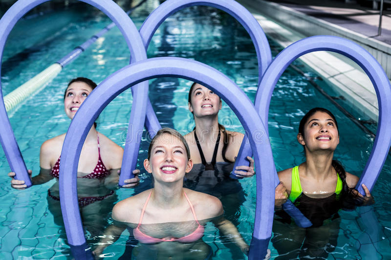 Happy fitness class doing aqua aerobics with foam rollers. In the pool stock images