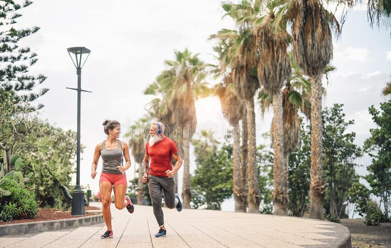 Happy fitness friends running at sunset outdoor - Couple of joggers training at evening time stock photo