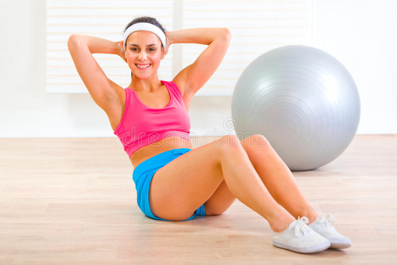 Happy fitness girl doing abdominal crunch on floor royalty free stock photo
