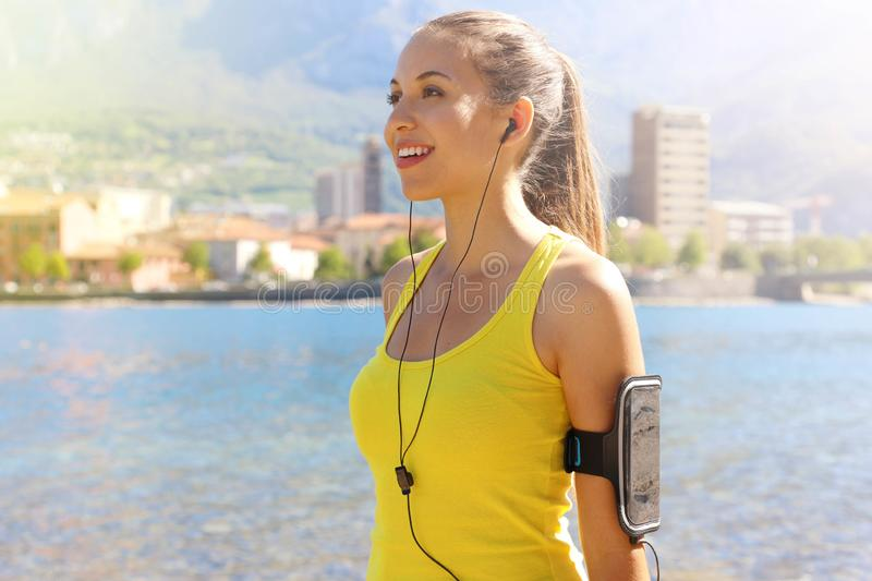 Happy fitness woman living a fit healthy lifestyle. Young girl wearing activewear and sports armband for phone and earphones, tech stock image