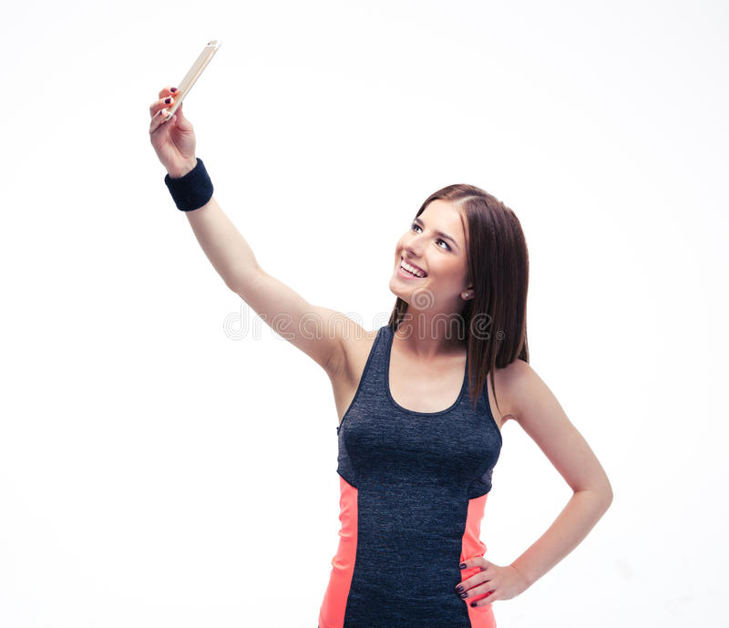 Happy fitness woman making selfie photo. On smartphone isolated on a white background royalty free stock image