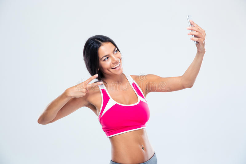 Happy fitness woman making selfie photo. On smartphone over gray background stock images