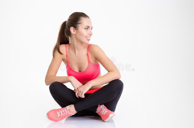 Happy fitness woman sitting with folded legs and looking away stock image