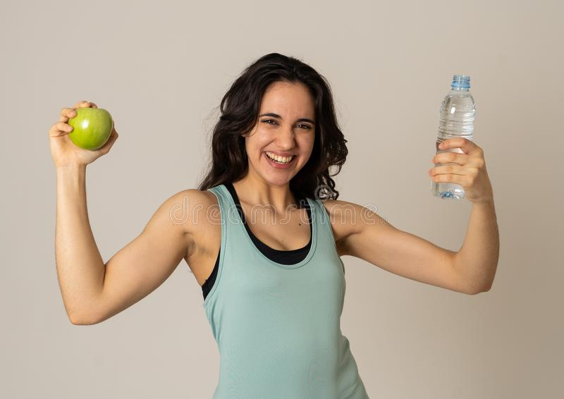 Portrait of attractive latin fitness model with apple and water feeling healthy and fit stock image