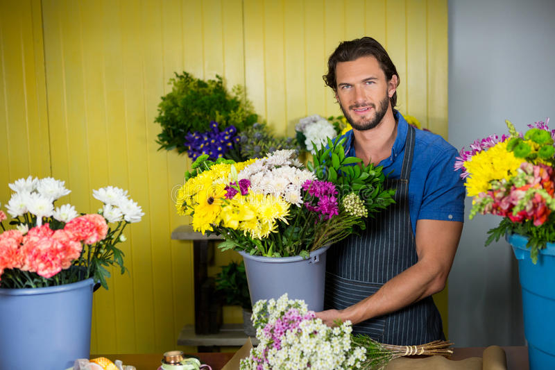 Happy florist holding bucket of flower royalty free stock images