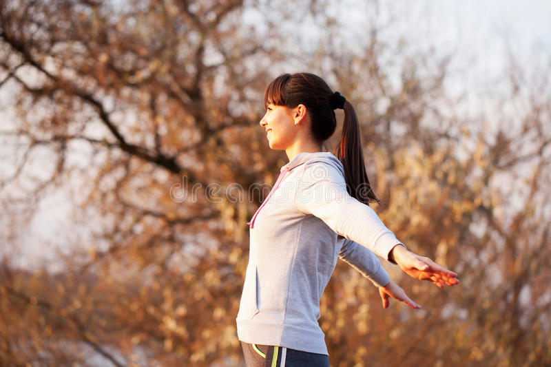 Happy flying middle-aged woman looking at sunset,. Happy flying middle-aged woman looking at the sunset, arms outstretched to the sides. Healthy lifestyle stock photography