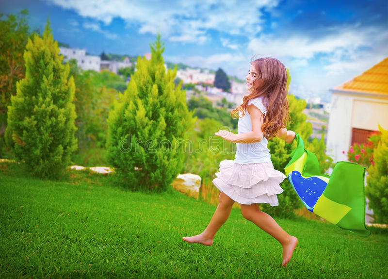 Happy football fan. Cute little girl running on backyard with national Brazil flag, sportive childhood, football championship concept stock photography