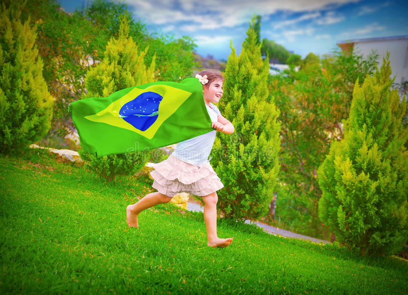 Happy football fan. Cute little girl running on backyard with national Brazil flag, sportive childhood, football championship concept royalty free stock photography