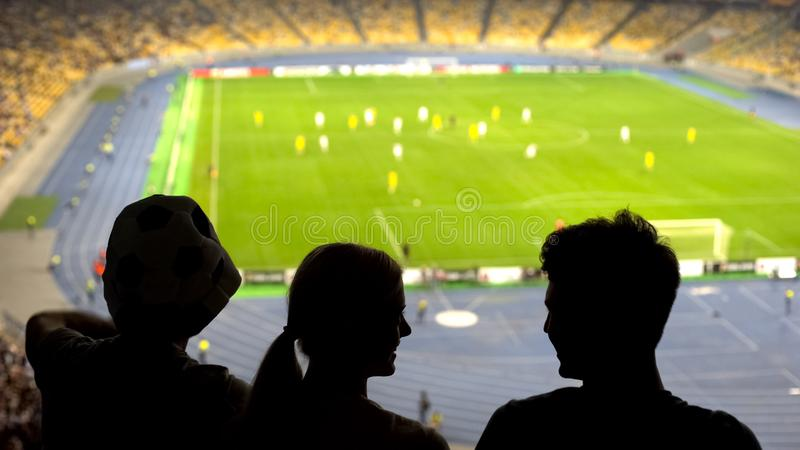 Happy football fans watching game and supporting team at stadium podium, league royalty free stock images