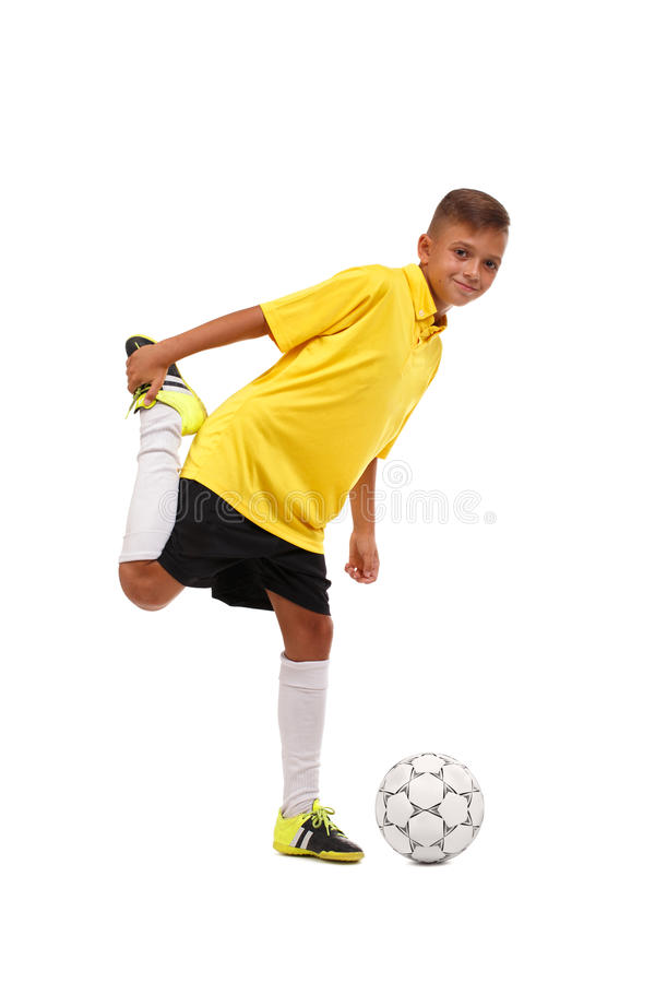 A happy footballer is warming up. A cheerful child in a football uniform isolated on a white background. Full-length stock photos