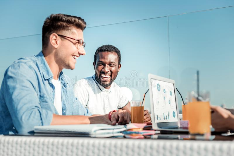 Happy foreigner looking at his friend stock photo
