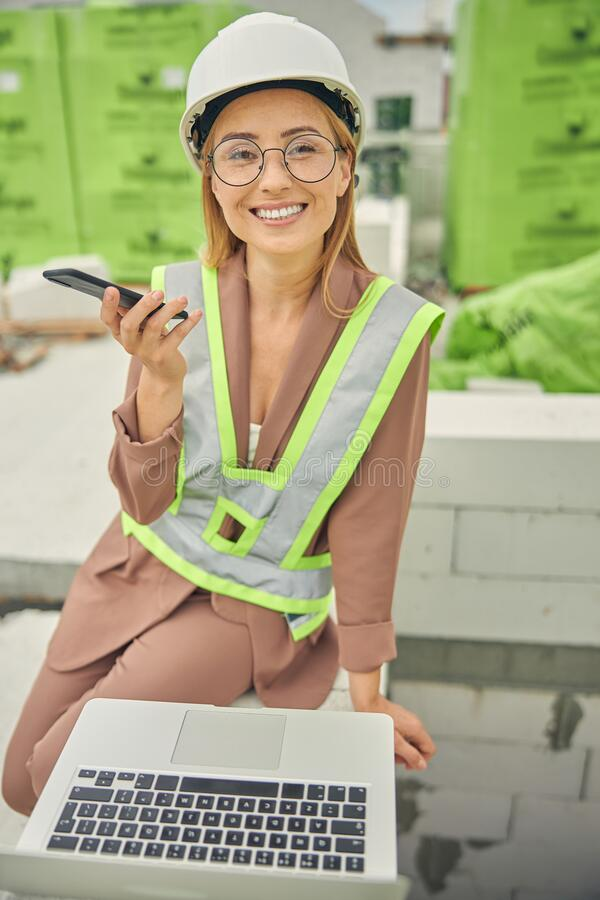 Free Happy Forewoman With A Cellphone Smiling At The Camera Stock Photos - 194144313