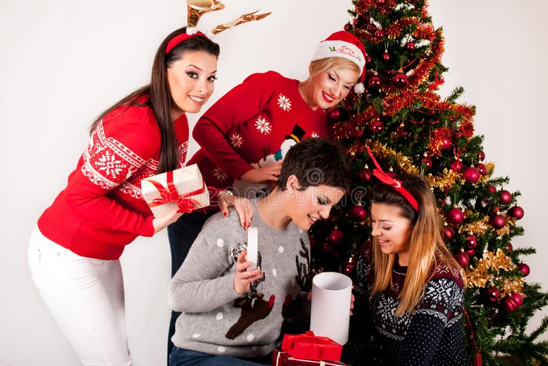 Happy Four Girls with gift boxes and Christmas tree. Happy Four Girls in wool sweater with gift boxes and Christmas tree and decoration. Xmas and New Year royalty free stock image