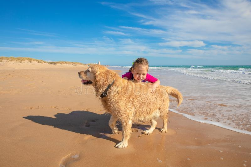 Happy little girl playing with a dog on the seashore of beach royalty free stock photos