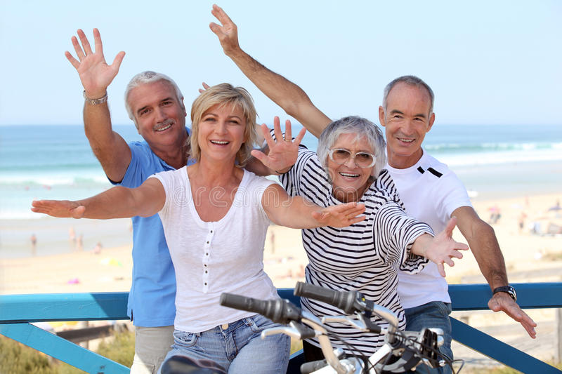 Happy foursome at the oceanfront stock photos