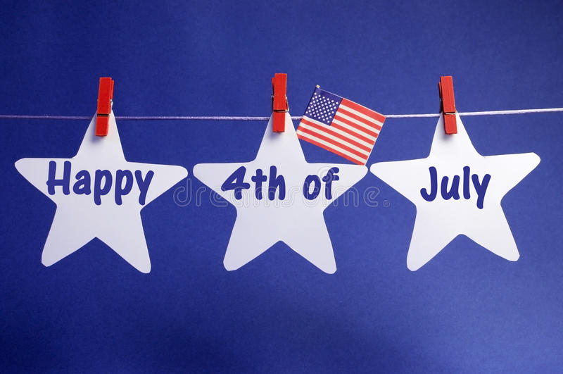 Happy Fourth 4th of July message written across three 3 white stars with USA American flag hanging on red pegs on a line royalty free stock image