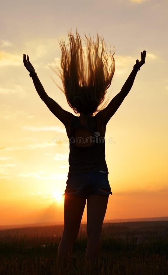Happy fröhliche Frau mit langen Haaren, die bei Sonnenuntergang die Hände auf der Wiese ausbreiten stockfoto