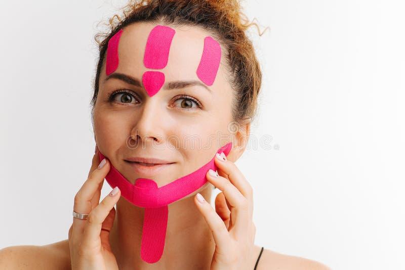 Happy Frau mit Kosmetikaufkleber auf ihrem Gesicht, von den Effekten befreit, berührt Gesicht lizenzfreies stockbild