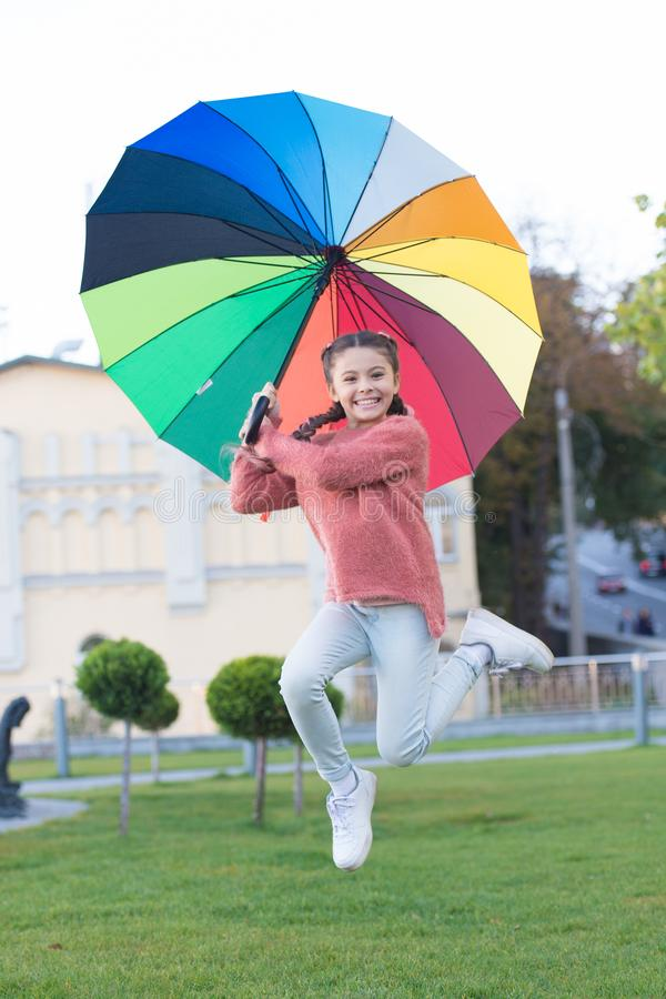 Happy and free. cheerful child. Spring style. Rainbow after rain. Little girl under colorful umbrella. Positive mood in stock photo
