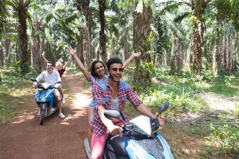Happy Free Couples Driving Scooter Enjoy Travel In Tropical Forest Cheerful Friends Road Trip royalty free stock image