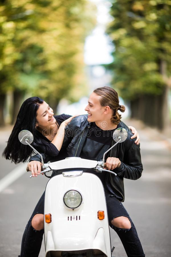 Happy free freedom couple driving scooter excited on summer holidays vacation. Couple ride scooter and look each other royalty free stock photography