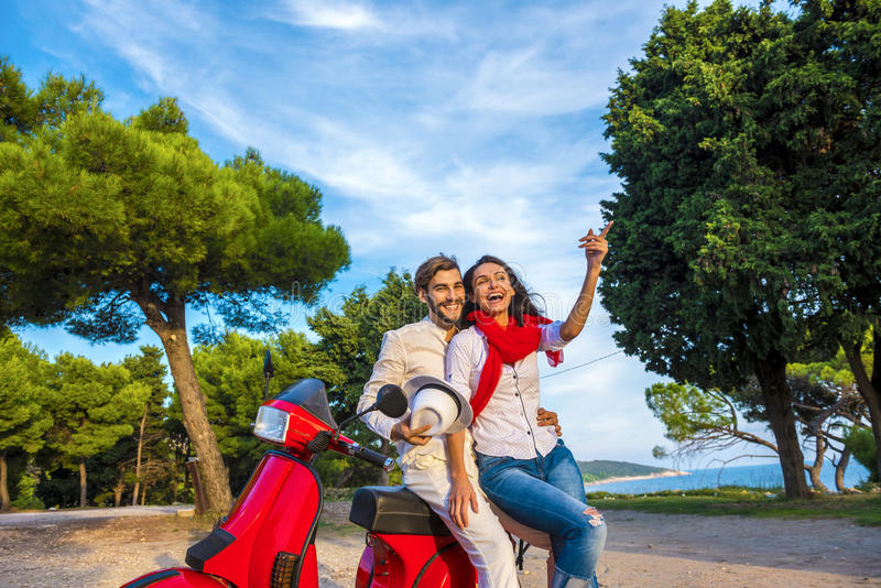 Happy free freedom couple driving scooter excited on summer holidays vacation. royalty free stock images