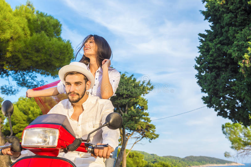 Happy free freedom couple driving scooter excited on summer holidays vacation. stock photo