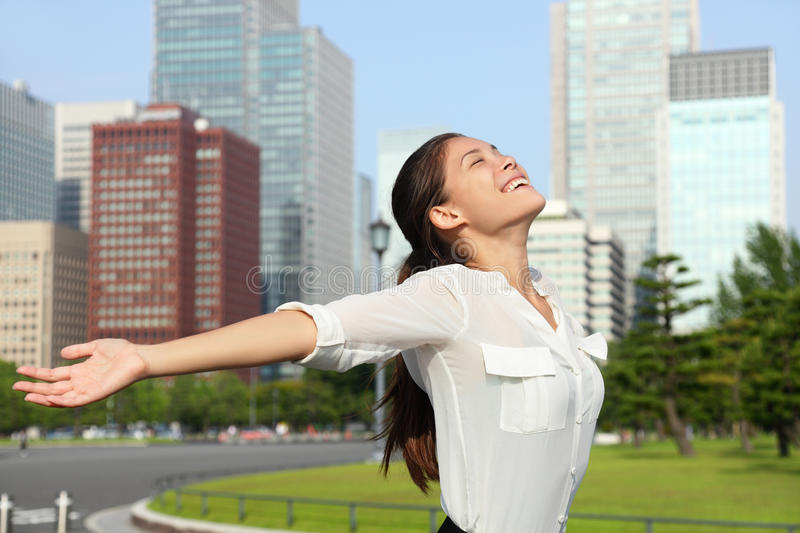 Happy free japanese business woman in Tokyo, Japan. Freedom success businesswoman - Happy free japanese business woman in Tokyo city skyline. Carefree Asian royalty free stock image