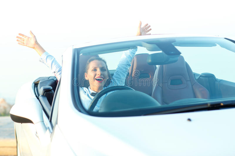 Happy free woman in cabriolet cheering joyful with arms raised stock photos