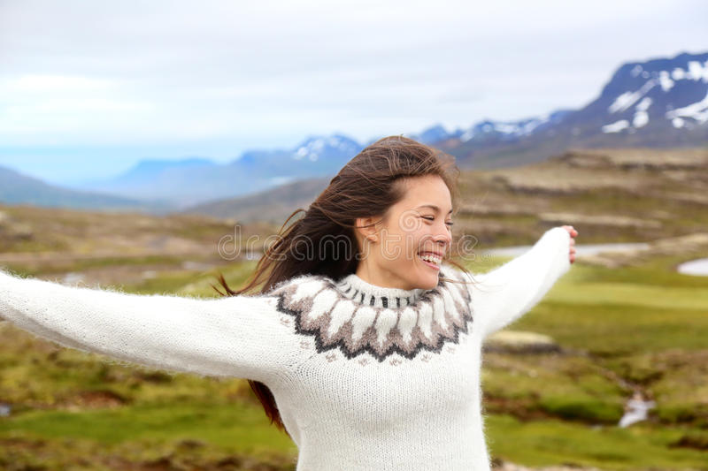 Happy free woman on Iceland in Icelandic sweater. Portrait of girl happy smiling outdoors in nature wearing Icelandic sweater. Pretty Asian Caucasian stock photography