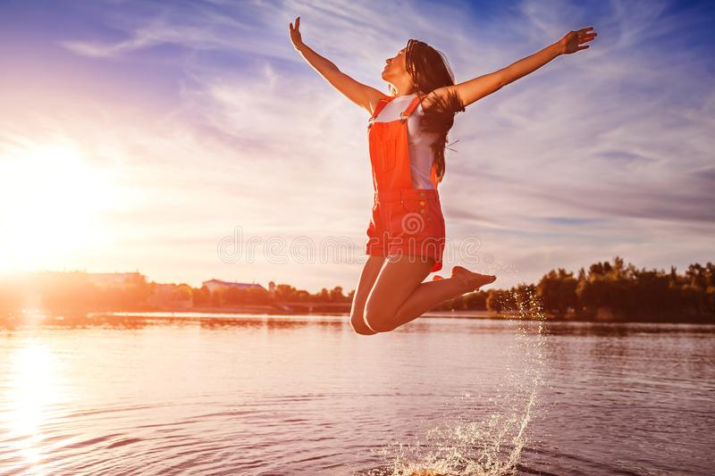 Happy and free young woman jumping and raising arms on river bank. Freedom. Active lifestyle stock photography