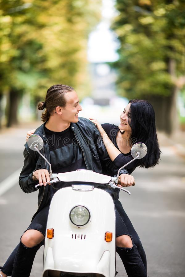 Happy free freedom couple driving scooter excited on summer holidays vacation. Couple ride scooter and look each other. Happy freedom couple driving scooter royalty free stock images