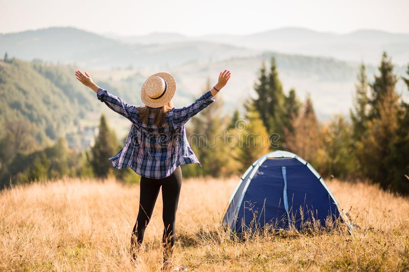 Happy freedom girl in straw hat with hands up in mountains travel royalty free stock photo