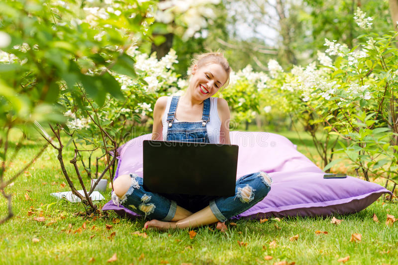 Happy freelancer working in the garden. Writing, surfing in the internet using laptop. Young woman relaxing and having royalty free stock image