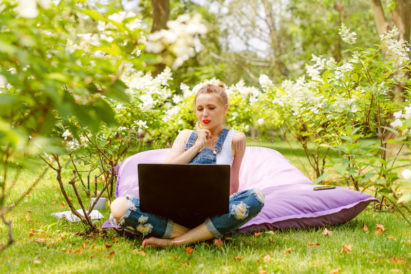 Happy freelancer working in the garden. Writing, surfing in the internet using laptop. Young woman relaxing and having stock photos