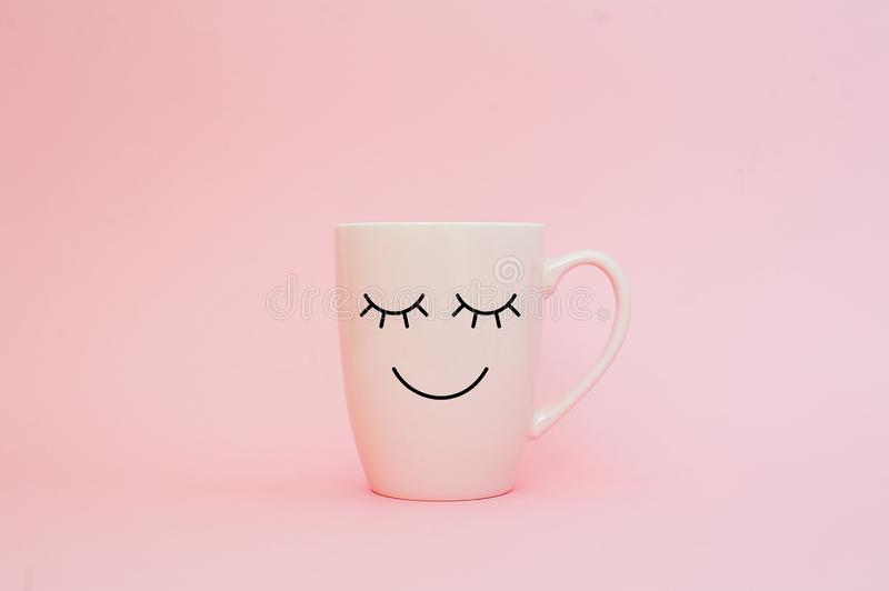 Happy friday word. Cup of coffee on pink background with smile face on mug. Concept about love and relationship. stock photos