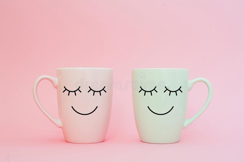 Happy friday word. Two cups of coffee stand together to be heart shape on pink background with smile face on cup. stock photos