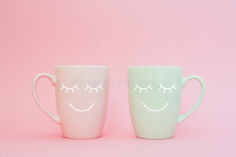 Happy friday word. Two cups of coffee stand together to be heart shape on pink background with smile face on cup. royalty free stock photo