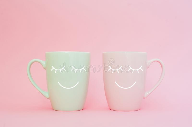 Happy friday word. Two cups of coffee stand together to be heart shape on pink background with smile face on cup. royalty free stock images