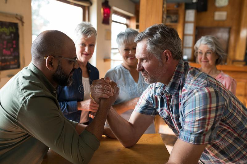 Happy friend arm wrestling each other. In a bar royalty free stock photography