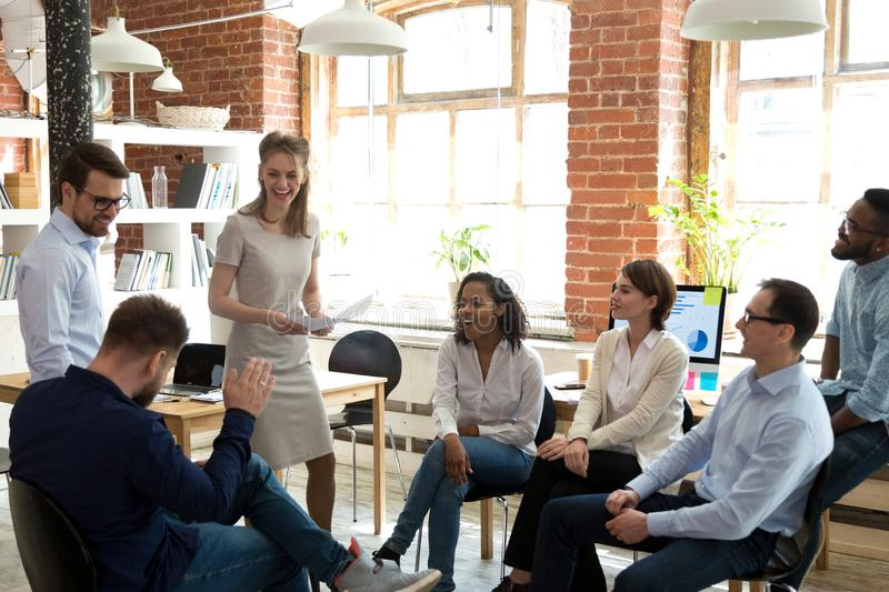 Happy friendly business team having fun at corporate training. Funny teambuilding activity, diverse employees group laughing at briefing, colleagues joking stock image